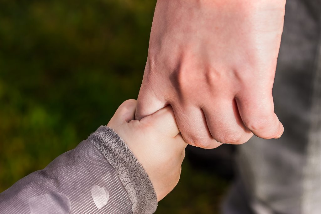 adult and child holding hands