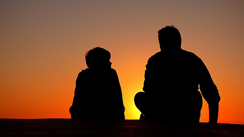 Father and son talking, sunset in back ground