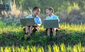 Two boys laughing while holding computers