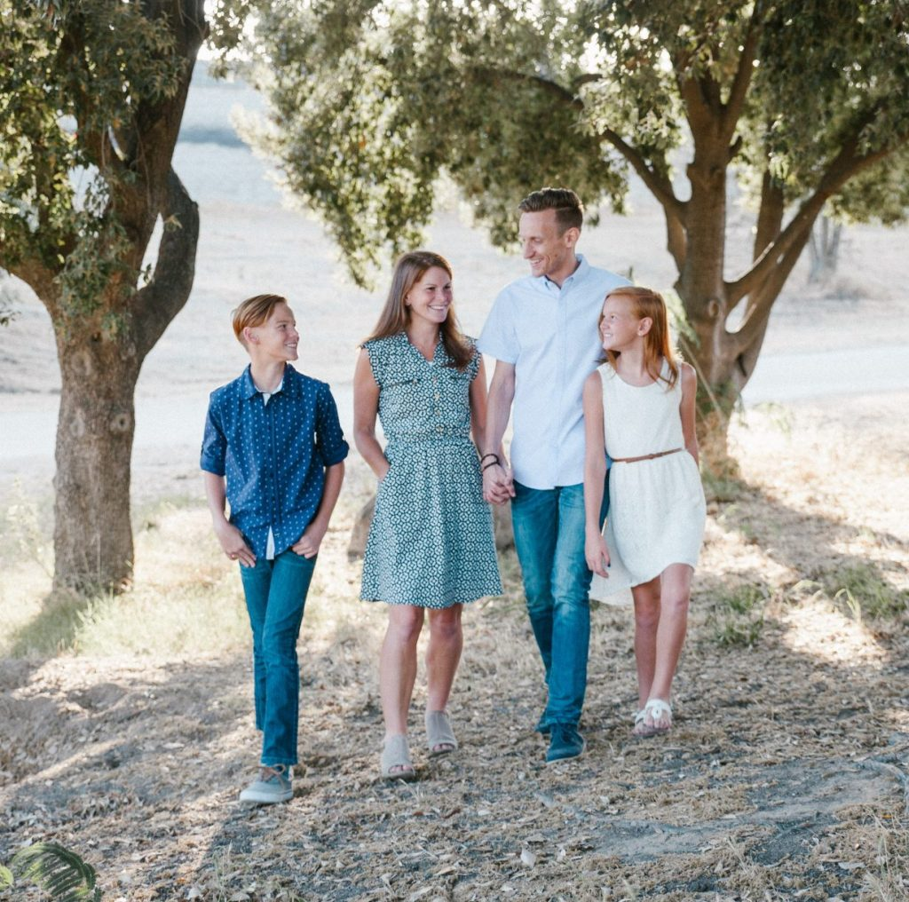 family of four walking under trees