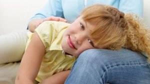 Smiling girl laying on woman's knee