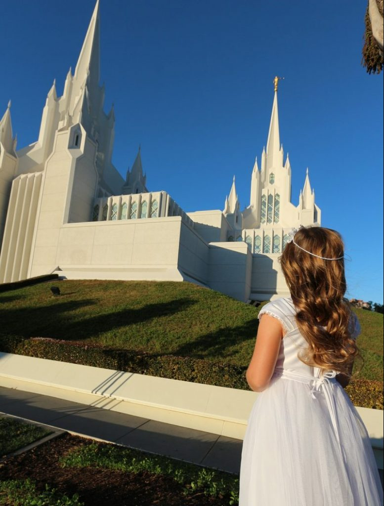 Girl in white dress looking at the San Diego Temple of the Church of Jesus Christ of Latter-day Saints