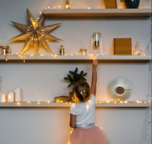 Child in from of shelves with christmas lights