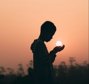 Boy with hands that look like they are holding the setting sun