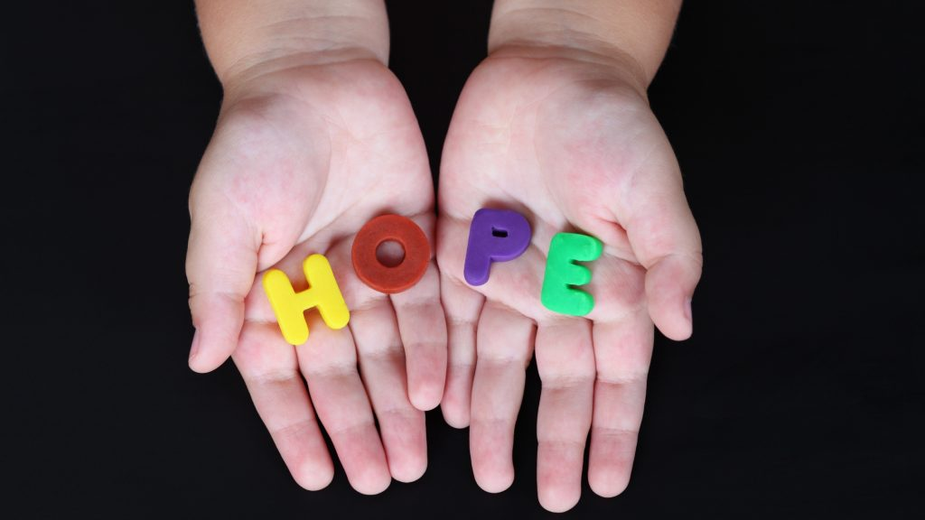 Toy letters in a child's hands spelling hope. How to teach your children hope.