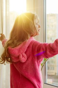 girl opening the curtains looking out of window