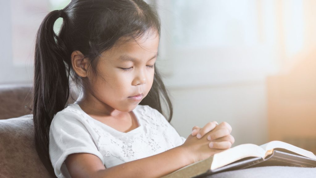 Little girl reading and praying